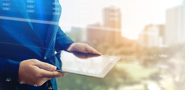 1025744818 istock photo Reflection Businessman using tablet analyzing data and economic growth graph chart. Concept on tablet with hologram. 1148648921