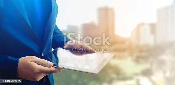 1025744818 istock photo Reflection Businessman using tablet analyzing data and economic growth graph chart  and copy space. Concept on tablet with hologram. 1148648975