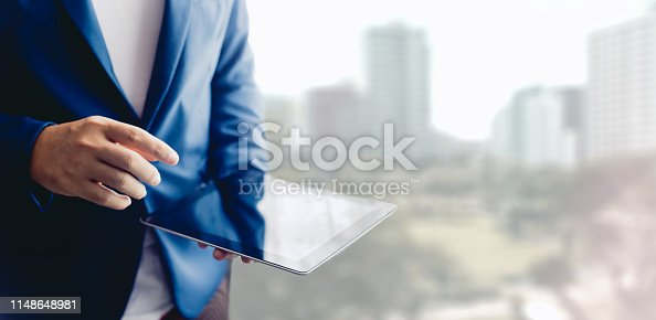 1025744818 istock photo Reflection Businessman using tablet analyzing data and economic growth graph chart. Concept on tablet with hologram. 1148648981