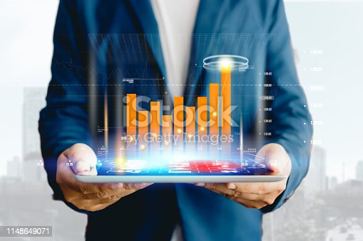 1025744818 istock photo Reflection Businessman using tablet analyzing data and economic growth graph chart. Concept on tablet with hologram. 1148649071