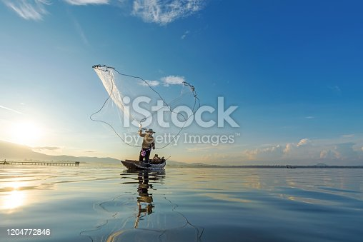 istock Reflection fisherman action when fishing net with dry alone tree on the boat in the lake outdoors sunshine morning blue sky background.  Agriculture Industry 1204772846