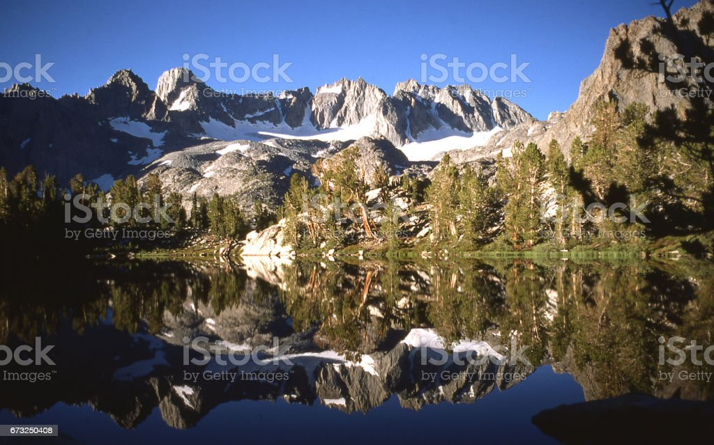 Reflection in a lake in the Sierra Nevada Mountains west of Big Pine California with the Palisade Crest and Mount Sill in the background stock photo
