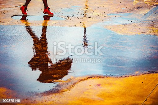 Reflection in a puddle of a young woman holding umbrella, walking outdoors over an empty yellow parking lot on a cold, windy, rainy autumn day.