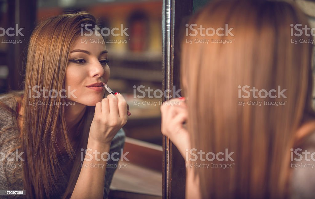 Reflection in mirror of a beautiful woman applying lipstick. stock photo