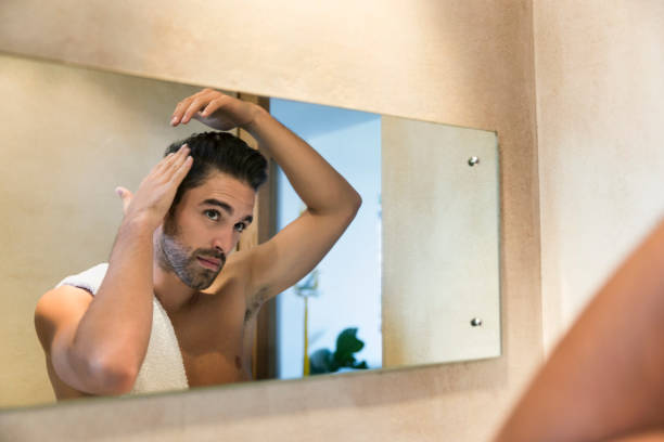 Reflection in mirror of young man fixing his hair stock photo