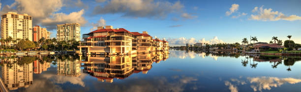 Reflection in the water of buildings along the Village at Venetian Bay Reflection in the water of buildings along the Village at Venetian Bay in Naples, Florida. naples florida stock pictures, royalty-free photos & images