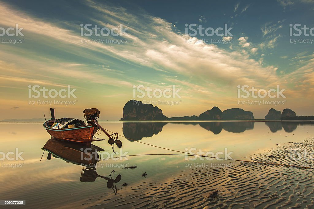 Reflection long tail boat over colorful sky on the beach stock photo