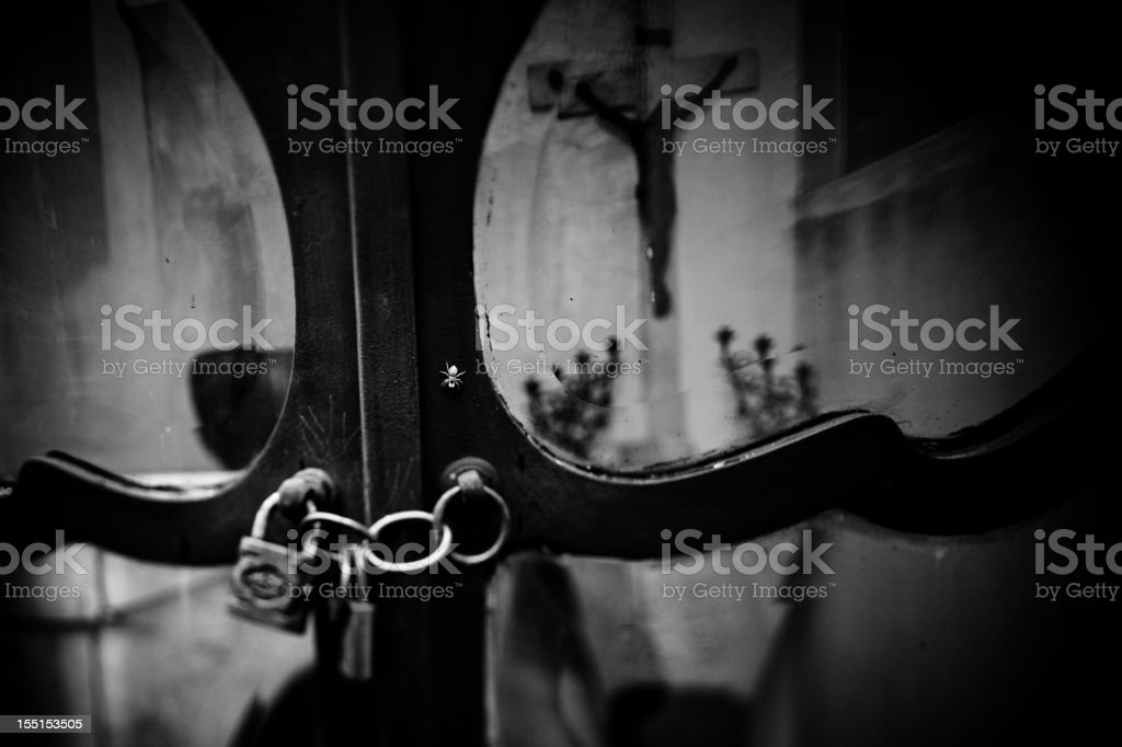 Reflection of a crucifix and locked tomb royalty-free stock photo