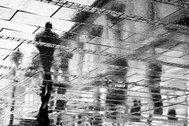 Reflexion eines Mannes in regnerischen Gehweg Pflaster – Foto
