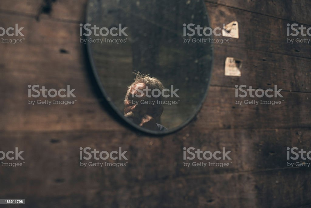 Reflection of an elderly man in a mirror stock photo