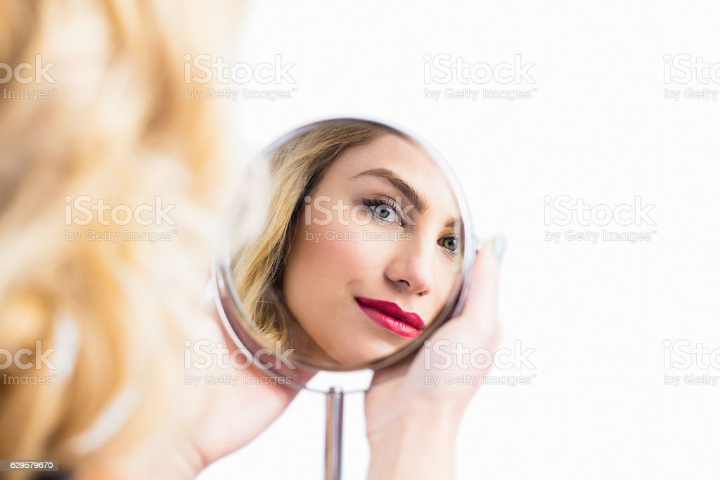Reflection of beautiful woman in hand mirror stock photo