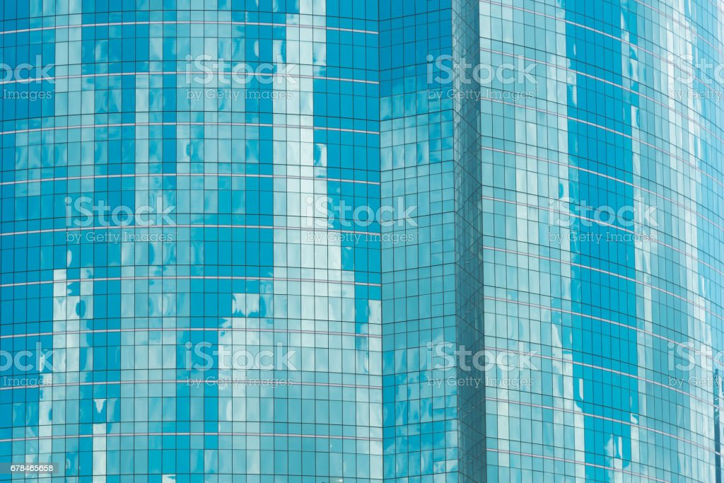 Reflection of blue sky with clouds in the windows. Facade of a modern office building. Modern industrial building with glass. Abstract background. royalty-free stock photo