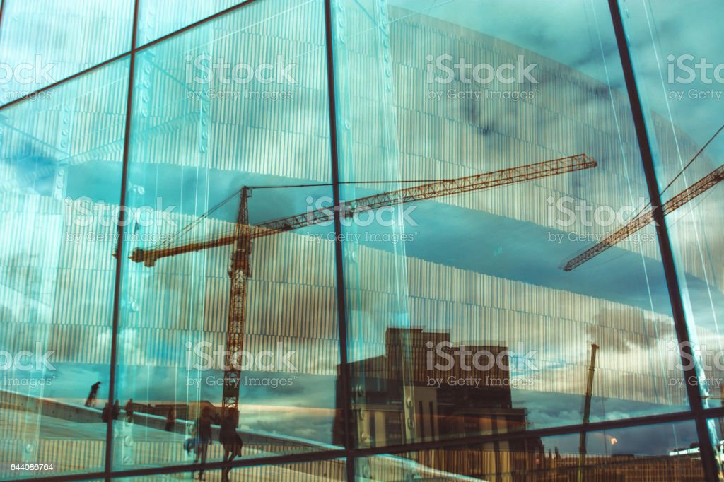 Reflection of buildings and cranes, walking people in window stock photo