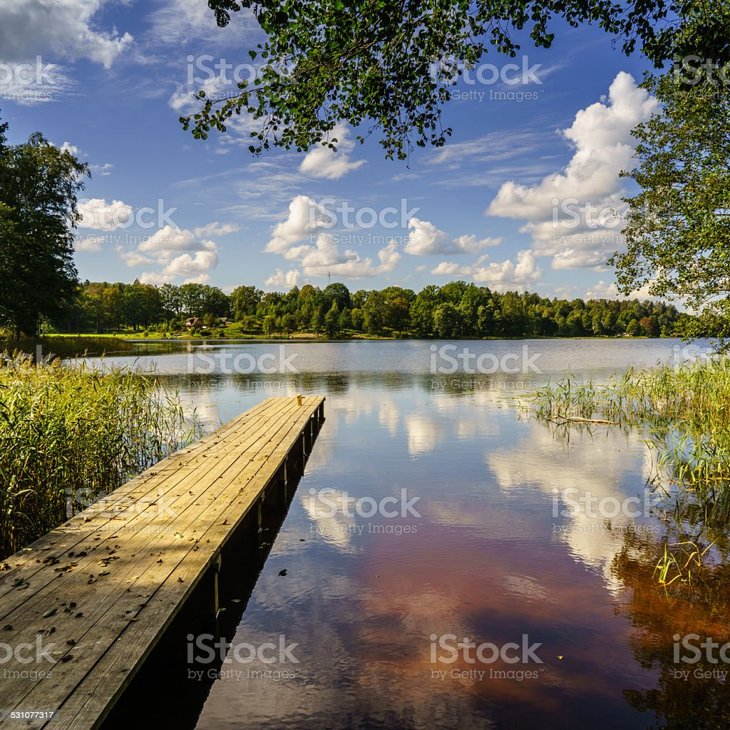reflection of clouds in the lake with boardwalk stock photo