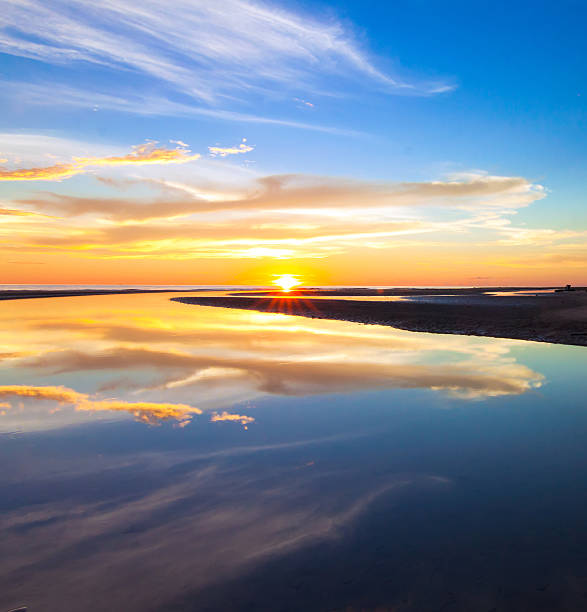 Reflection of colorful sunset at a tropical beach stock photo
