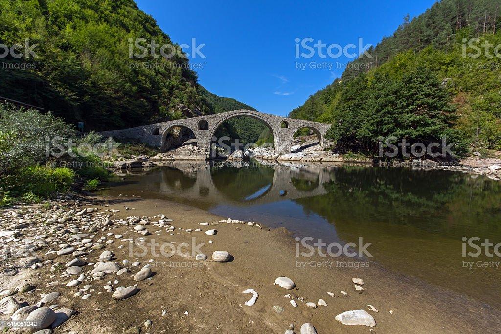 Reflection of Devil's Bridge and Rhodopes mountain in Arda river stock photo
