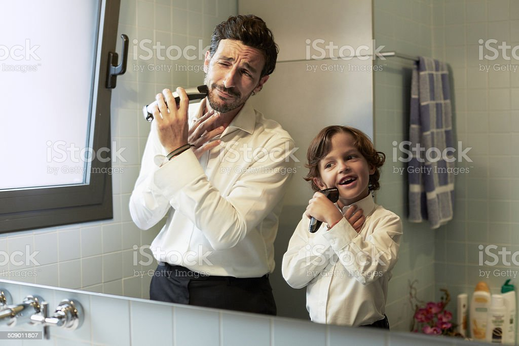 Reflection of father and son shaving together stock photo