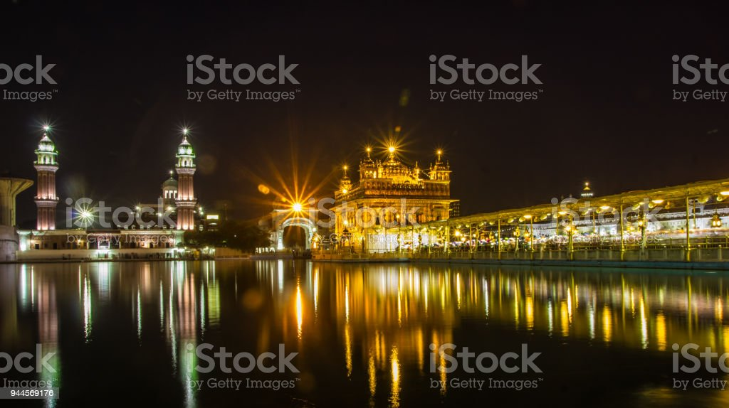 reflection of golden temple at night on water surface of nearby lake stock photo