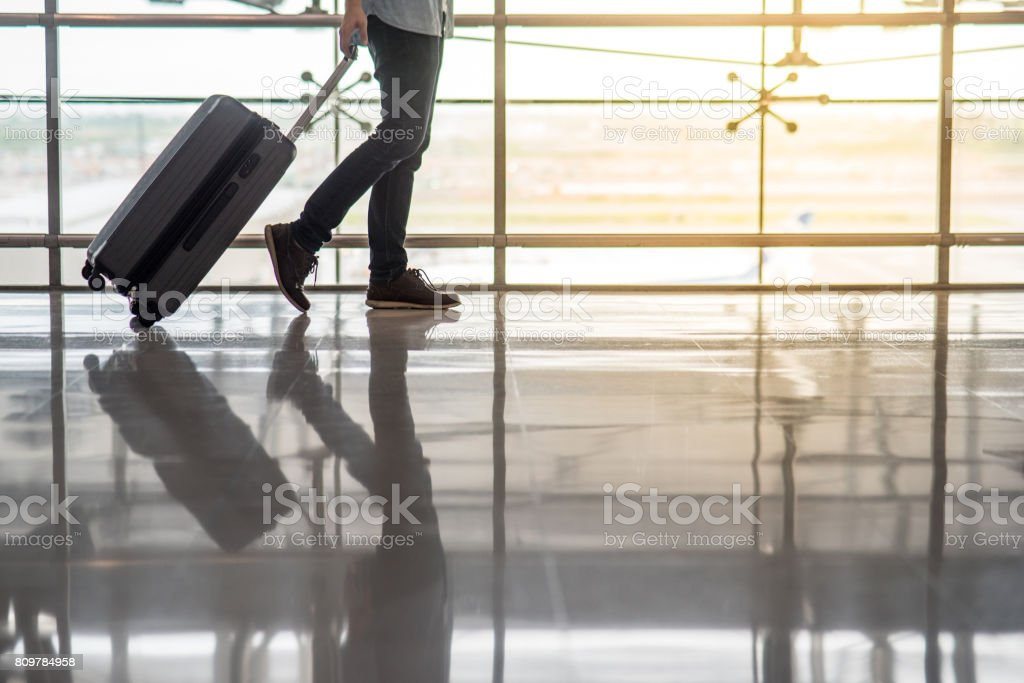 Reflection of half male body walking in the airport terminal with suitcase luggage stock photo