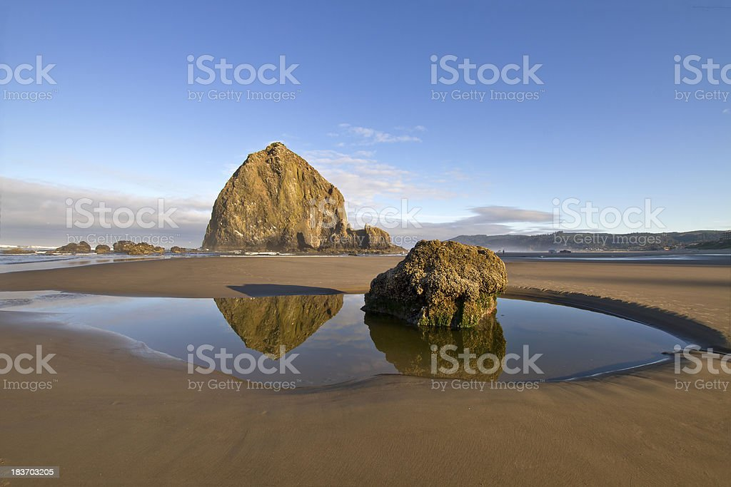 Reflection of Haystack Rock at Cannon Beach stock photo