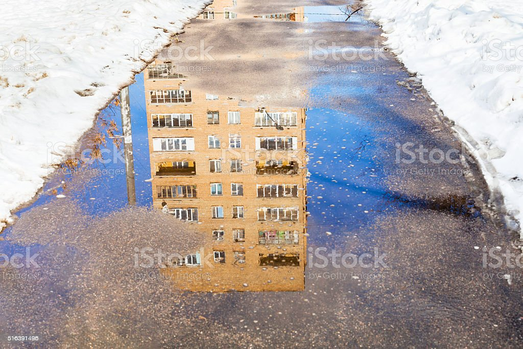 reflection of house in puddle of melting snow stock photo