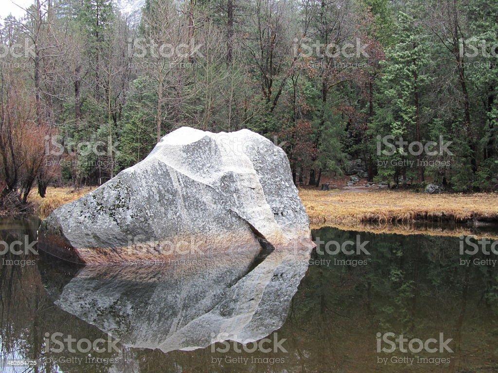 Reflection of huge rock at lake stock photo