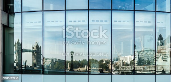London, United Kingdom - September 28, 2014: The skyline of London from the Tower Bridge up to the modern buildings of the Financial District (the building of Swiss Re - aka the Gurkin - is located on the very right) is reflected in the windows of an office building on September 28, 2014 in London, UK.