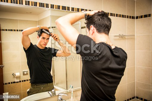 istock Reflection of Man Bushing Hair in Mirror 478838034