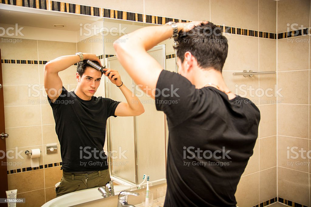 Reflection of Man Bushing Hair in Mirror stock photo