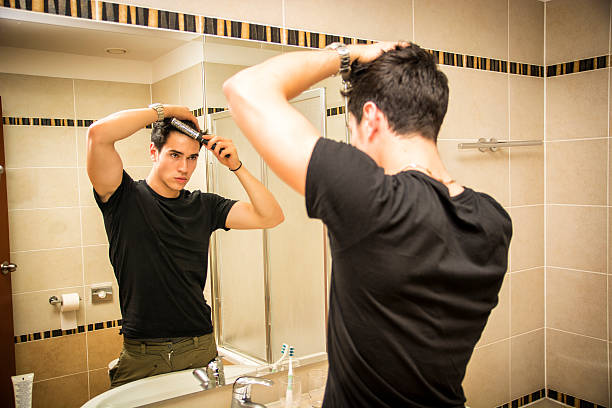 Reflection of Man Bushing Hair in Mirror Reflection of Young Man Bushing Hair in Bathroom Mirror Getting Ready to Go Out combing stock pictures, royalty-free photos & images
