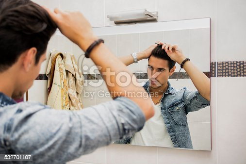 istock Reflection of Man Bushing Hair in Mirror 532701107