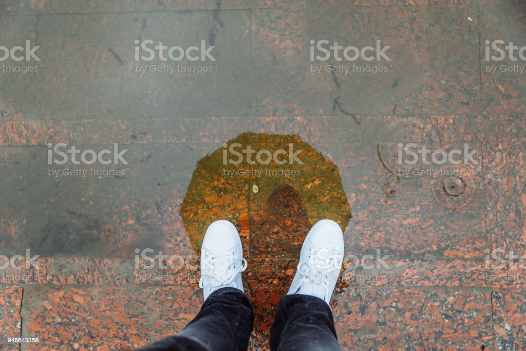 reflection of man with yellow umbrella in white sneakers in puddle stock photo