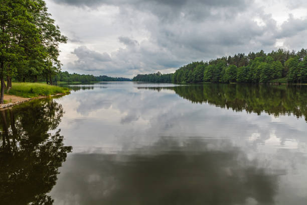 Reflection of moody sky in calm lake stock photo