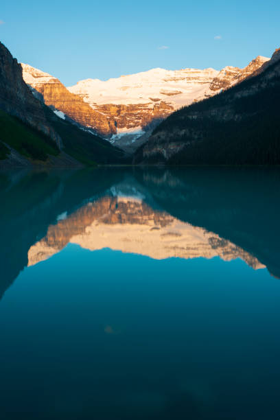 Reflection of Mount Victoria in Lake Louise at sunrise Reflection of Mount Victoria in Lake Louise at sunrise, Banff National Park, Canada mt victoria canadian rockies stock pictures, royalty-free photos & images