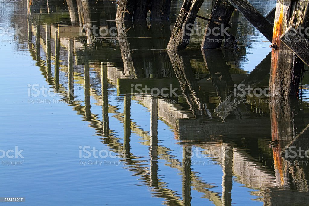 Reflection of old walkway in water stock photo