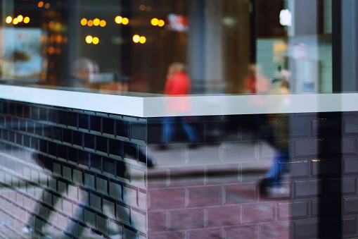 Reflection of passers-by on the street in glass