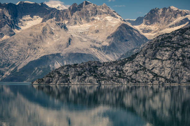 Reflection of rugged mountains in the Alaska inside passage stock photo