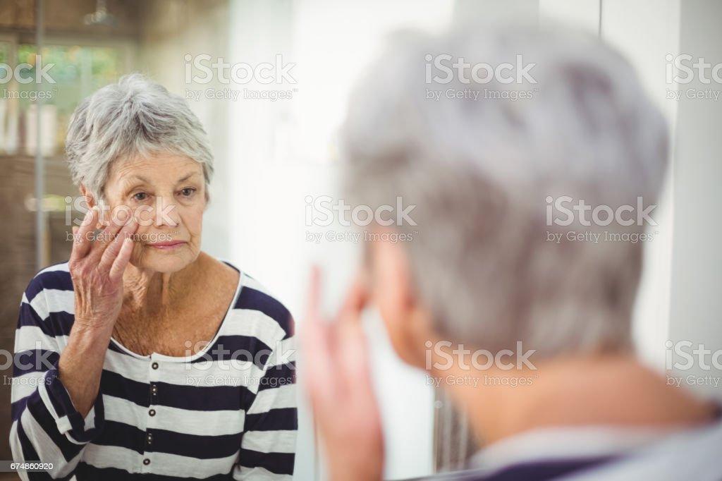 Reflexión de mujer senior en piel en espejo - foto de stock