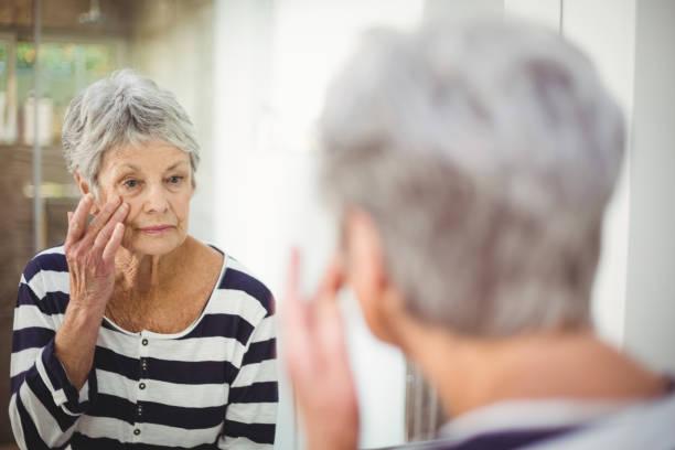 reflexion der senior frau haut im spiegel betrachten - alte spiegel stock-fotos und bilder