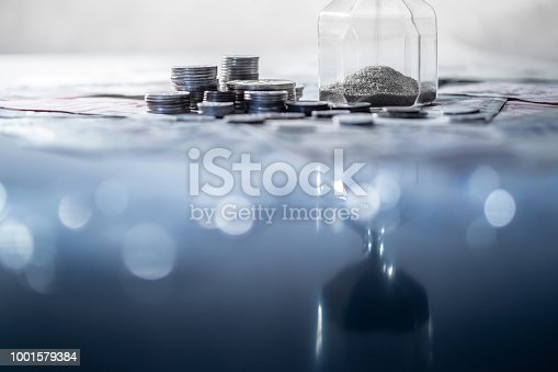 istock Reflection of sliver sand running through the shape of modern hourglass on glowing table with currency. Time investment and passing time. Urgency countdown timer for business deadline concept 1001579384