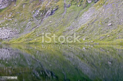 reflection of stones on the mountain in the water of the lake