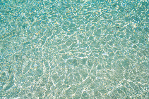 Reflection of sun light on shallow water and sand under it on beach of Isla de Perro Island in Caribbean See, Panama