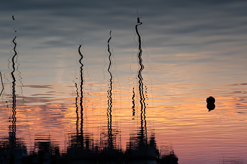 Reflection of the masts and hulls of yachts in the calm waters of a harbour