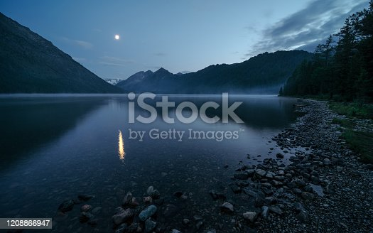 Reflection of the moon in a mysterious foggy lake. Wild russian nature. Beautiful landscape with lake in the mountains. Traveling in the Altai Republic. Active tourism in Russia. Multa Lake.