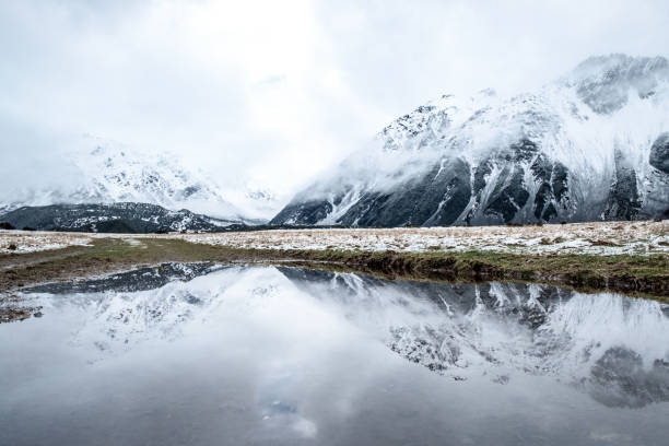 A reflection of the mountain on the water in Mount Cook Village valley covered with white snow after a snowy day. stock photo