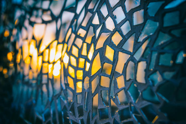 Reflection of the setting sun in the mirror pieces of glass mosaic - abstract background - shallow depth of field stock photo