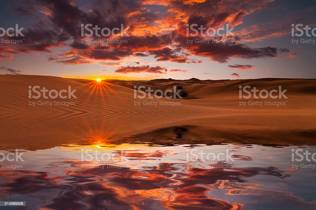 Reflection of the sunset sky and sand dunes stock photo