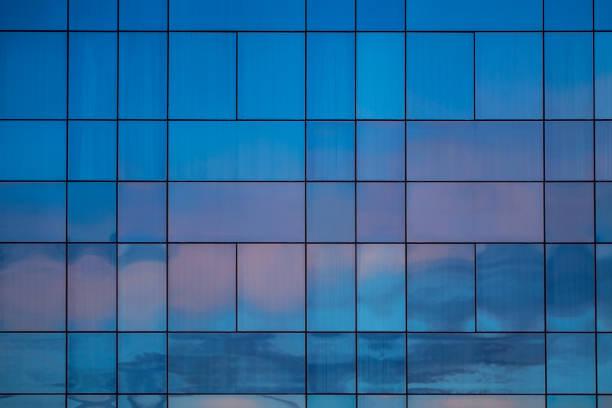 reflexion von den sonnenuntergang himmel auf einer fassade von kristallen in den farben lila und blau - fensterfront stock-fotos und bilder