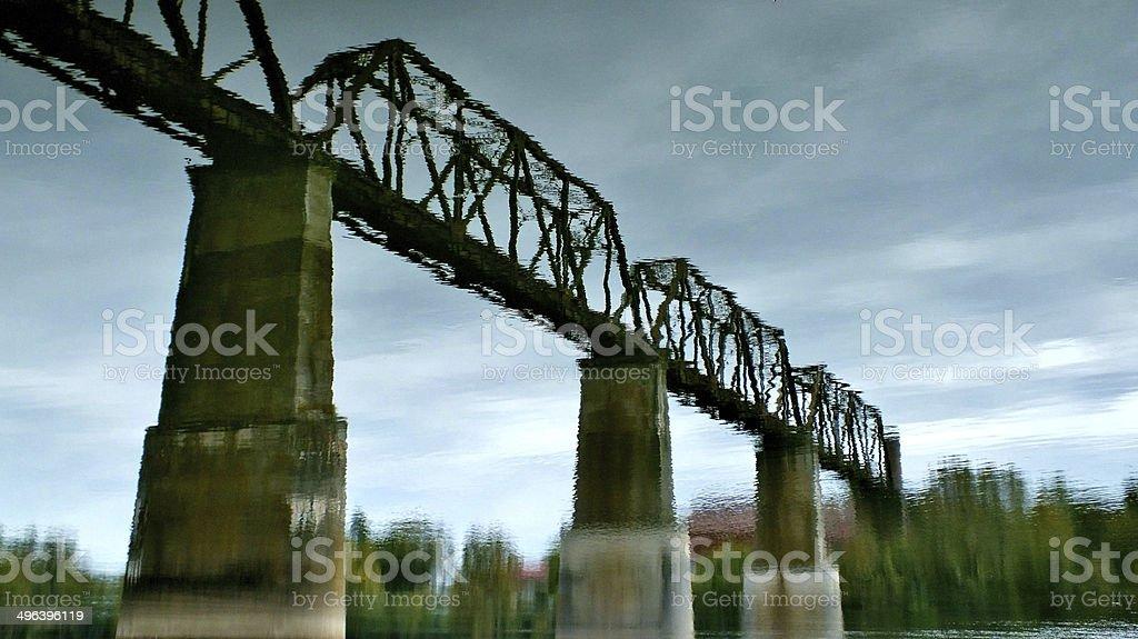 Reflection of train bridge in river stock photo
