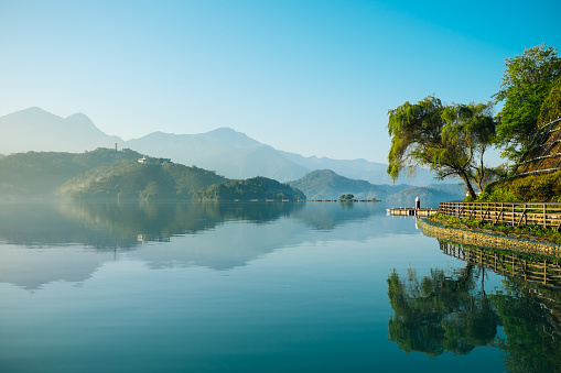 Reflection of trees, mountains, and islands on the clear water lake, sun moon lake.